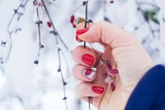 Valentine day nail art design manicure. Female hand with bright red heart manicure holding red berries on a winter background. Trendy red nails with design royalty free stock photography