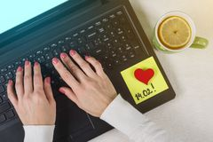Valentine Day. A note of text 14.02 written on a paper sticker. Background computer, laptop, woman`s hands on the keyboard. Royalty Free Stock Photos