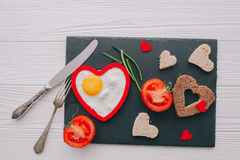 Valentine day.romantic breakfast.fried egg. Valentine day.romantic breakfast. fried egg, bread and vegetables on shate board Stock Images