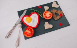 Valentine day.romantic breakfast.fried egg. Valentine day.romantic breakfast. fried egg, bread and vegetables on shate board Stock Photos