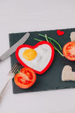 Valentine day.romantic breakfast.fried egg. Valentine day.romantic breakfast. fried egg, bread and vegetables on shate board Royalty Free Stock Photography