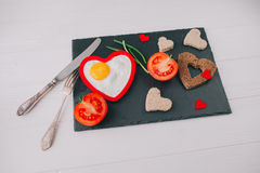 Valentine day.romantic breakfast.fried egg. Valentine day.romantic breakfast. fried egg, bread and vegetables on shate board Royalty Free Stock Images