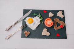 Valentine day.romantic breakfast.fried egg. Valentine day.romantic breakfast. fried egg, bread and vegetables on shate board Royalty Free Stock Photo