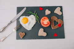 Valentine day.romantic breakfast.fried egg. Valentine day.romantic breakfast. fried egg, bread and vegetables on shate board Royalty Free Stock Photos
