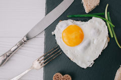 Valentine day.romantic breakfast.fried egg. Valentine day.romantic breakfast. fried egg, bread and vegetables on shate board Stock Image