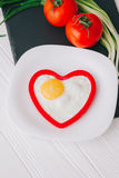 Valentine day. Romantic breakfast. Fried egg, bread and vegetables on wooden tray Stock Photos