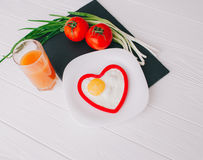 Valentine day.romantic breakfast. Fried egg, bread and vegetables on wooden tray Royalty Free Stock Photo