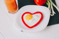 Valentine day.romantic breakfast. Fried egg, bread and vegetables on wooden tray Royalty Free Stock Image