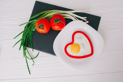 Valentine day.romantic breakfast. Fried egg, bread and vegetables on wooden tray Stock Photography