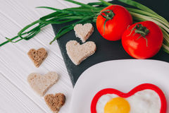 Valentine day.romantic breakfast. Fried egg, bread and vegetables on wooden tray Royalty Free Stock Images