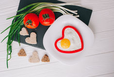 Valentine day.romantic breakfast. Fried egg, bread and vegetables on wooden tray Stock Image