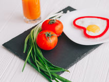 Valentine day.romantic breakfast. Fried egg, bread and vegetables on wooden tray Stock Photos