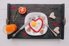 Valentine day.romantic breakfast. Fried egg, bread and vegetables on wooden tray Royalty Free Stock Photos