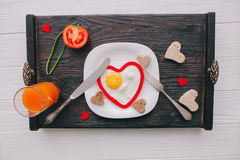 Valentine day.romantic breakfast. Fried egg, bread and vegetables on wooden tray Stock Photo