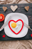 Valentine day. romantic breakfast. Fried egg, bread and vegetables on wooden tray Royalty Free Stock Photo