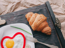 Valentine day.romantic breakfast. Fried egg, bread and vegetables on wooden tray Royalty Free Stock Photography
