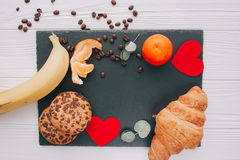 Valentine day.romantic breakfast. Fruits ,coffee and cookies on shate board Stock Images