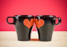 Valentine day series, cups of milk with decorative heart on wood table and red background Royalty Free Stock Photography