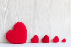 Valentine Day. Sewed pillow hearts row border on red clothespins white background. Stock Images