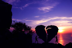 Valentine day, Silhouette couples are pushing the broken heart-shaped stone. Royalty Free Stock Photos
