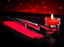 Valentine day table setting with knife, fork, red burning heart shaped candle. On red hearts bokeh background royalty free stock photos