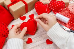 Valentine Day tema Arbetsplats för att förbereda handgjorda garneringar Den bästa sikten av kvinnliga händer syr filthjärta Packa royaltyfri foto