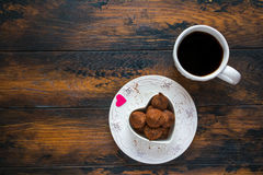 Valentine day, white vintage plate, sweets and heart made from red paper, cup of black coffee. Stock Photos