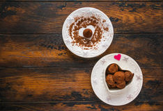 Valentine day, white vintage plates, sweets and hearts made from red paper and grated chocolate. Royalty Free Stock Photography