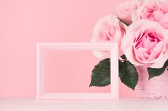 Valentine days mockup with blank frame for text and design - romance bouquet of roses and wooden pink frame on white wood table. royalty free stock images