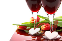 Valentine decoration. With two glasses of wine, white hearts and colorful tulips on white background Stock Photography