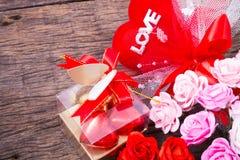 Valentine decoration, chocolate box, roses, heart and love word. Valentine decoration, chocolate box, roses, ribbon, heart and love word on wooden table top Stock Photos