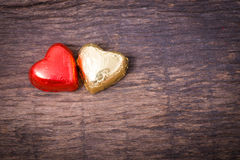 Valentine decoration, couple heart shaped chocolate,red and gold. Valentine decoration, couple heart shaped chocolate, red and golden on wooden table top Stock Photo
