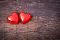 Valentine decoration, couple red heart shaped chocolate. On wooden table top Royalty Free Stock Photo