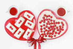 Valentine dessert. For two. Two cups of red beverage and cakes with cherries Stock Photo