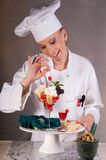 Valentine Dessert Chef. Close up of an attractive female Dessert Chef spiking a cherry atop an elegant dessert plate with white and dark chocolate hearts and Royalty Free Stock Image