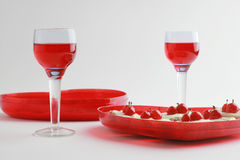 Valentine dessert two. Two glasses of red beverage and cakes with cherries Royalty Free Stock Images