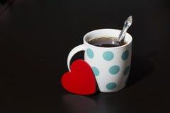Valentine en een kop thee in erwten op een donkere achtergrond royalty-vrije stock foto
