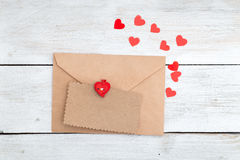 Valentine. envelope kraft paper and red hearts on a wooden backg Stock Image