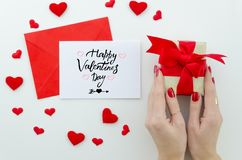 Valentine 14 february hand lettering greeting card. gentle composition for Valentine`s day woman hands holds gift box. With red bow, many little red hearts top royalty free stock photo