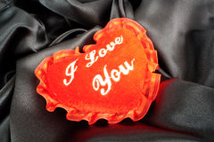Valentine fluffy heart pillow over black satin Royalty Free Stock Image