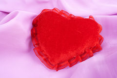 Valentine fluffy heart pillow over violet satin Royalty Free Stock Photo