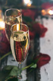 Valentine: Focus On Glass Of Champage With Roses Behind Stock Photography