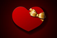 Valentine gift. Heart-shaped red gift box with golden bow on dark background. A Valentine's Day gift / wedding gift Stock Images