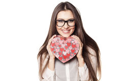 Valentine gift. Beautiful young woman with glasses posing with a heart shape gift stock photo