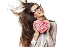 Valentine gift. Beautiful young woman with glasses and windy hair posing with a heart shape gift royalty free stock images