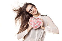 Valentine gift. Beautiful young woman with glasses and windy hair posing with a heart shape gift stock photo