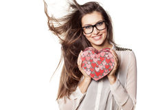 Valentine gift. Beautiful young woman with glasses and windy hair posing with a heart shape gift royalty free stock photography