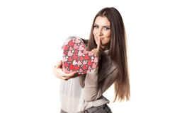 Valentine gift. Beautiful young woman posing with a heart shape gift and kissing her finger royalty free stock photography