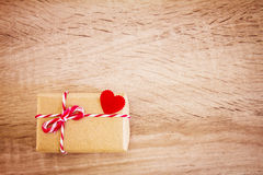 Valentine gift box concept with red heart on wooden background Stock Photos