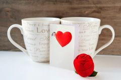 Valentine gift box with greeting card and two cups. On wooden background. Indoors close-up Stock Photo